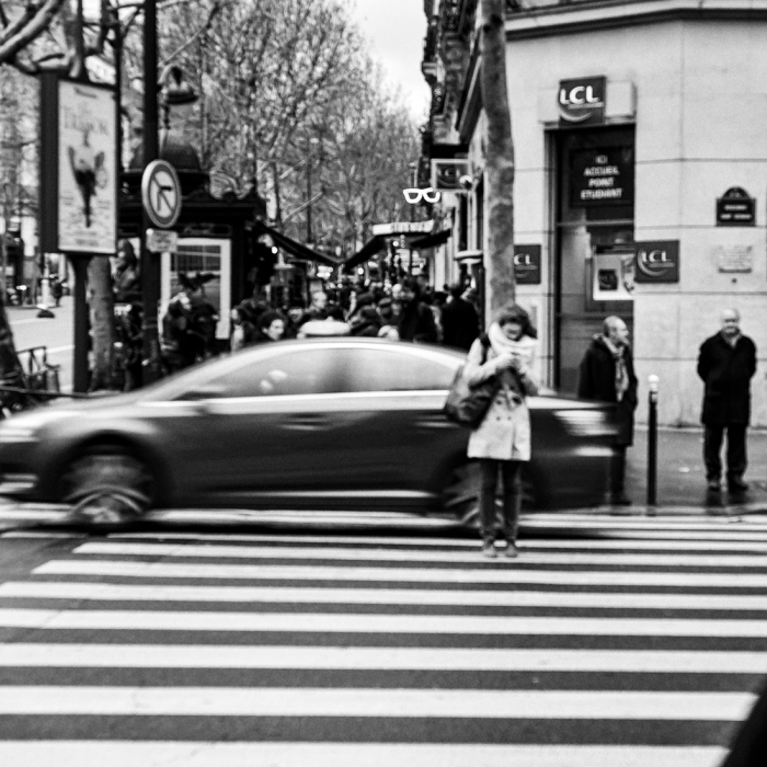 Moça destraída no celular parada no meio da rua em Paris.